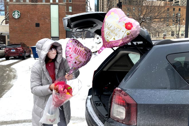 Ellen Yun loads Valentine's Day gifts for her mom, sister and brother in-laws, nephew and her two children Saturday, Feb. 13, 2021, outside a Chicago area grocery store. Yun said she had shopped for her husband earlier.