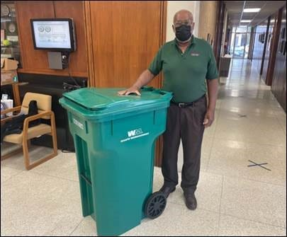 Smithville City Council member Bill Gordon poses with the new green poly-cart that will be used by the city's residential waste service customers starting in March for trash pickup. The poly-cart can hold 96 gallons.