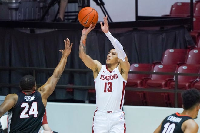 Feb 13, 2021; Tuscaloosa, Alabama, USA; Alabama Crimson Tide guard Jahvon Quinerly (13) shoots a three pointer against Georgia forward P.J. Horne (24) during the first half at Coleman Coliseum. Mandatory Credit: Marvin Gentry-USA TODAY Sports