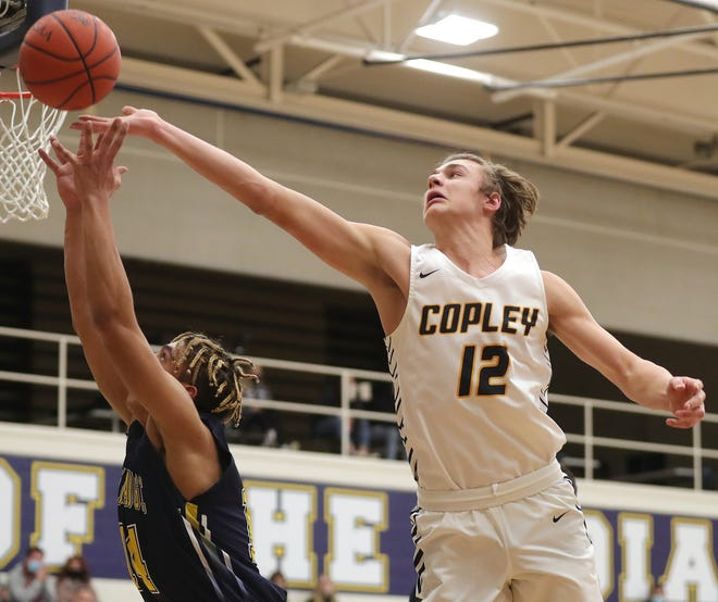 Copley's Caleb Laurich, right, swats the ball from the hands of Tallmadge's Collin Dixon during the first half of a basketball game, Saturday, Feb. 13, 2021, in Copley, Ohio. [Jeff Lange/Beacon Journal]