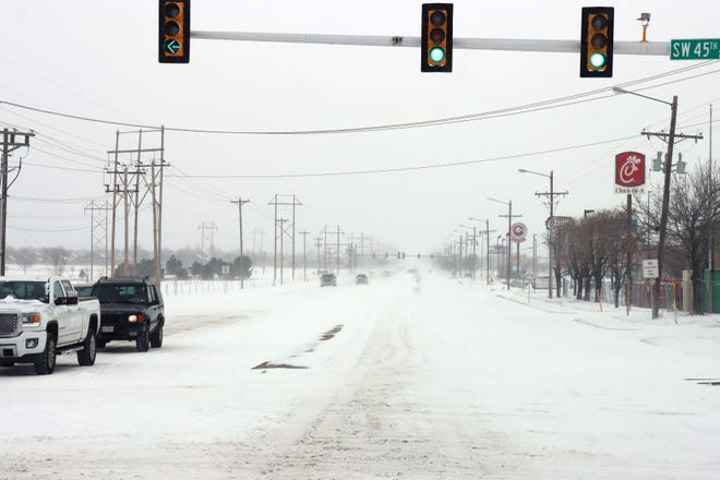 Motorists navigate the area of SW 45th Avenue and Coulter Street during Sunday's winter weather event.