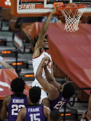 Texas forward Greg Brown scores over TCU center Kevin Samuel in February. After one season with the Longhorns, the former Vandegrift star has hired an agent and will go pro.