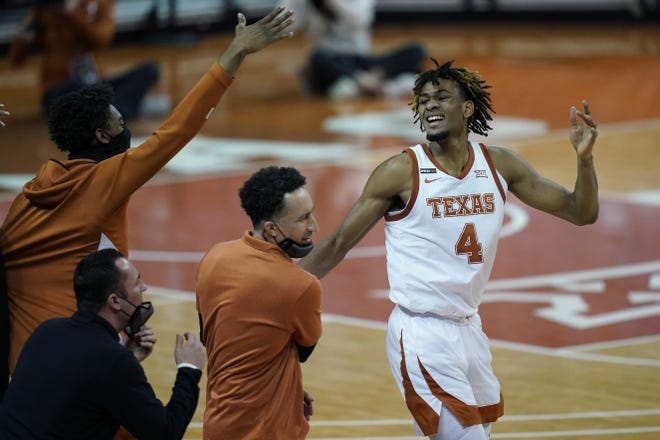 Texas forward Greg Brown celebrates a play with head coach Shaka Smart and teammates during the second half of Saturday's 70-55 win over TCU. The freshman scored 13 points in one of the most complete games of his young career.