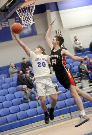 New Franklin junior Caleb Hull drives in for a layup in the first half Thursday night against Community in CAC action in New Franklin. The Bulldogs, winners of four straight, beat the Trojans 54-40.