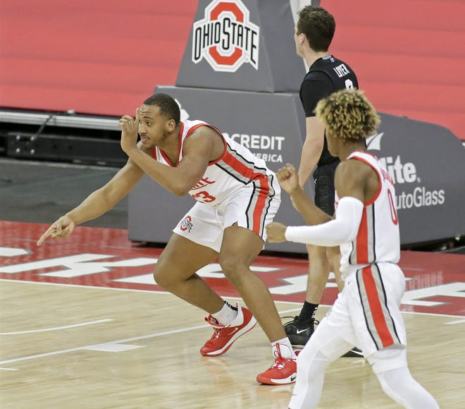"Ohio State center Zed Key (23) celebrates with ""finger guns"" after scoring and drawing a foul in a game against Michigan State on Jan. 31."