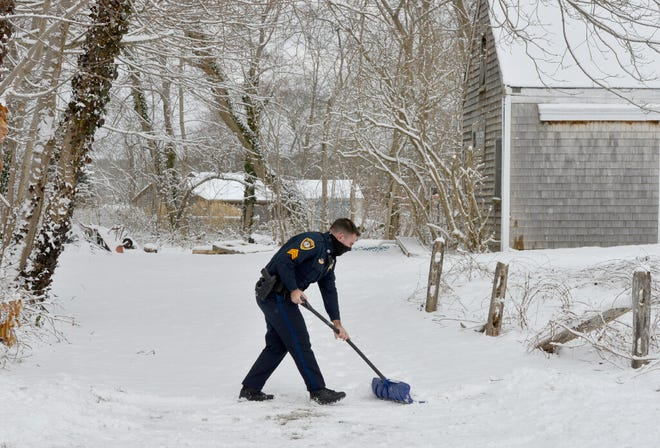 Eastham police Sgt. Josh Adams helps to clear snow out of a driveway at a home on Samoset Road.   Merrily Cassidy/Cape Cod Times