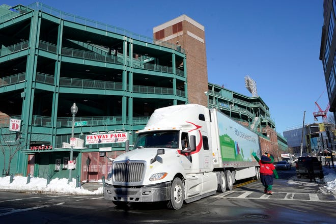 Wally the Green Monster, the team's mascot, waves as a Boston Red Sox equipment truck departs Fenway Park last Monday on its way to the team's spring training facility, in Fort Myers, Fla.