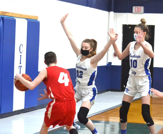 Mackinaw City's Larissa Huffman (middle) and Madison Smith (right) defend an Alba player during a game on Feb. 9. The Lady Comets improved to 3-0 with a victory over Engadine at home on Saturday.