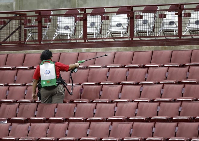 Amid the COVID-19 pandemic, member of the custodial crew disinfects the seats after an Ohio State women's basketball game against Maryland at Value City Arena in January.