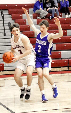 John Glenn's Blade Barclay (3) looks to pass with Cambridge's Owen Feldner (3) applying defensive pressure during Saturday night's game in New Concord.