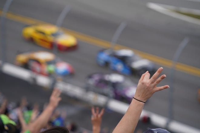 Fans raise three fingers to salute the late Dale Earnhardt on Lap 3 of the 2021 Daytona 500 on Sunday, Feb. 14, 2021, from Daytona International Speedway. A NASCAR legend, Earnhardt died on last-lap crash in the 2001 Daytona 500.