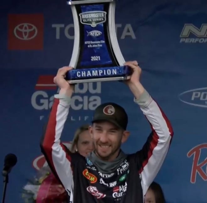 Belmont native Bryan New holds up a trophy won at the Bassmaster Elite Series event on the St. John's River in Florida.