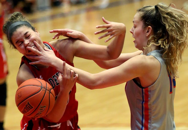 Hutchinson Community College's Kate Ogle (14) gets tangled up with Allen County's Endiah Byrd (10) as they battle for the rebound during their game Saturday night at the Sports Arena. HCC defeated Allen County 80-49.