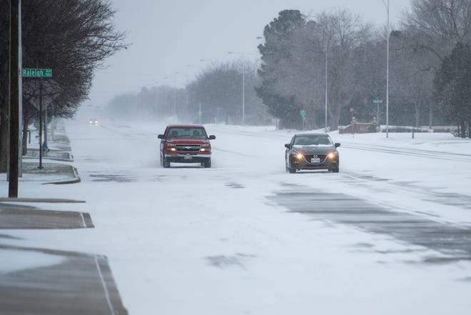 Vehicles make their way down 19th Street near Quaker Ave. while the snow comes down on Sunday, Feb. 14, 2021, in Lubbock, Texas.