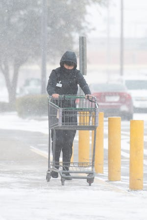 A sacker returns a cart at the Amigos on University Ave. on Sunday, Feb. 14, 2021, in Lubbock, Texas.