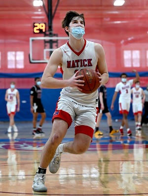 Natick's Ryan Mela is wide open as he prepares to dunk for two points during the Redhawks' last game of the season against Weston at Natick High School on Feb. 13, 2021.