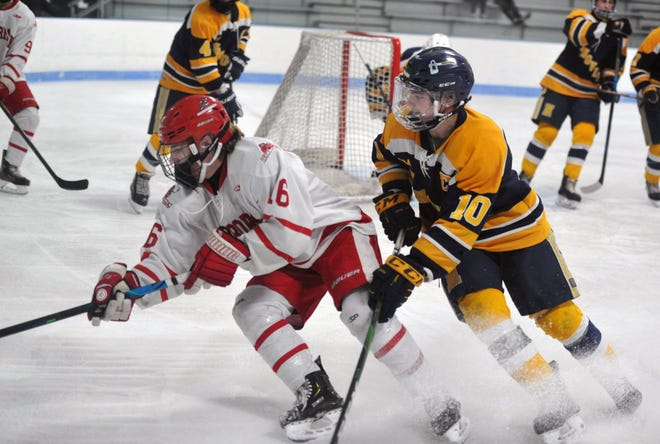 Hingham's Evan Corbett, left, and Hanover's Thao Lanagan race for a loose puck during boys ice hockey at the Hobomock Arena in Pembroke, Saturday, Feb. 13, 2021.