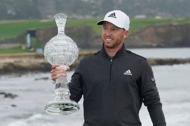 Daniel Berger holds up his trophy on the 18th green after winning the AT&T Pebble Beach Pro-Am golf tournament on Sunday in Pebble Beach, Calif.