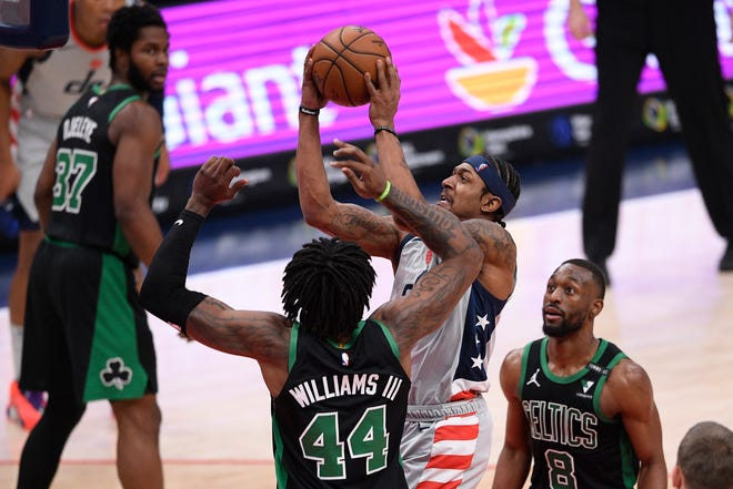 Wizards guard Bradley Beal goes to the basket against Celtics center Robert Williams III and guard Kemba Walker during the second half on Sunday in Washington. Williams was called for a foul on the play.