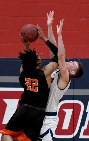 Findlay's Deven Stover is defended by Malone's Levi Seiler during a game in February.