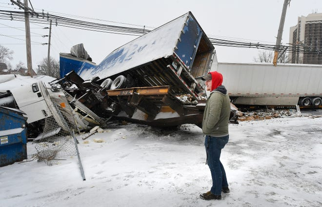 Illinois State University student Logan Meagher surveys damage after a freight train derailed near Hester St., south of Uptown Normal on Saturday. About 16 container cars came off the track blocking the main line through Normal.