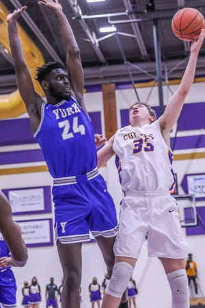 Kansas Wesleyan's Trey Duffey (33) puts up a shot over York's Webster Simeus (24) during Saturday's game at Mabee Arena.