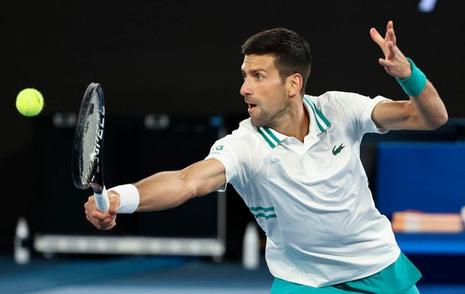 Novak Djokovic hits a backhand return to Milos Raonic during their fourth-round match at the Australian Open.