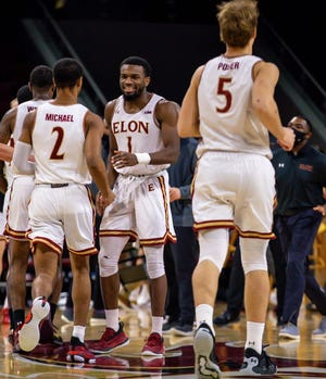 Elon's Chuck Hannah greets teammate Ja'Dun Michael, left, at the start of a timeout during last week's loss to James Madison. Elon claimed its first victory in CAA play with Sunday's defeat of College of Charleston.