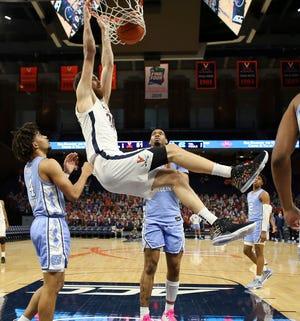 Virginia's Jay Huff dunks between North Carolina's RJ Davis, left, and Garrison Brooks, back, during Saturday night's game at John Paul Jones Arena.