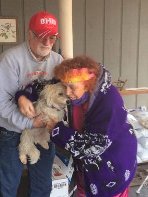 LaWanna Rine accepts the dog from Larry Kolakowski of New Philadelphia, who delivered the recovered animal to her in North Carolina.