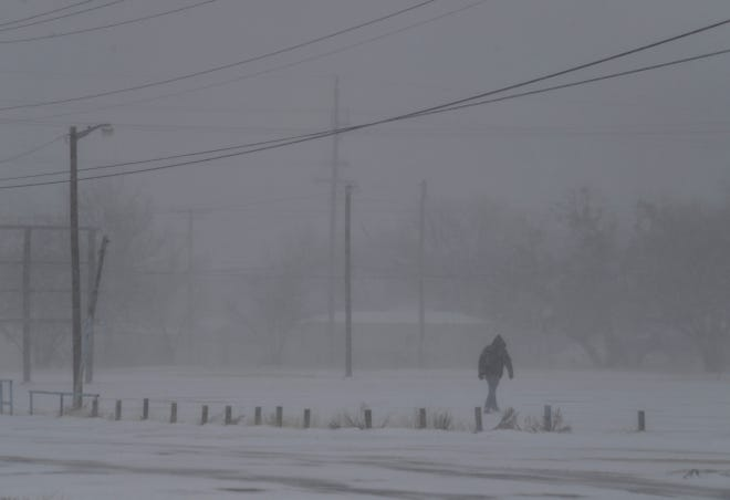 A figure crosses a parking lot in the blowing snow at North Second and Shelton streets Sunday. Wind picked up, creating blizzard-like conditions in Abilene.