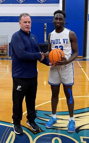 Paul VI senior Wisler Sanon, right, is congratulated by head coach Tony Devlin after scoring his 1,000th career point during the Eagles victory over Winslow on Friday.