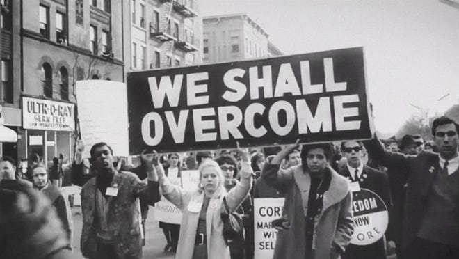 """""""We Shall Overcome"""" reads a banner at a march."""