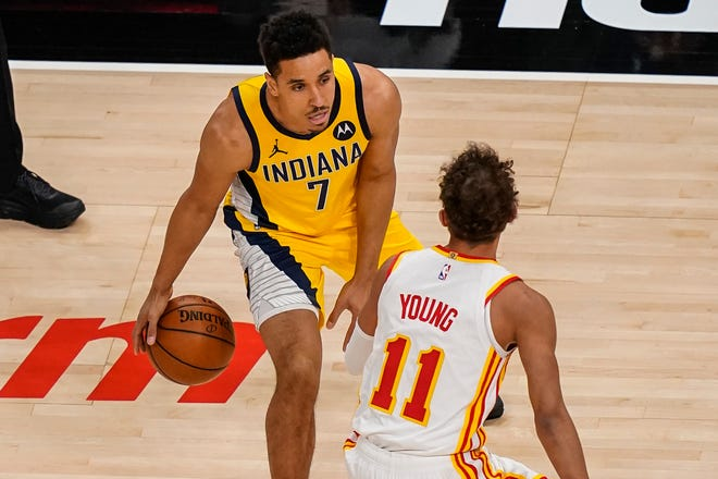 Indiana Pacers guard Malcolm Brogdon (7) dribbles the ball against Atlanta Hawks guard Trae Young (11) during the first quarter at State Farm Arena.