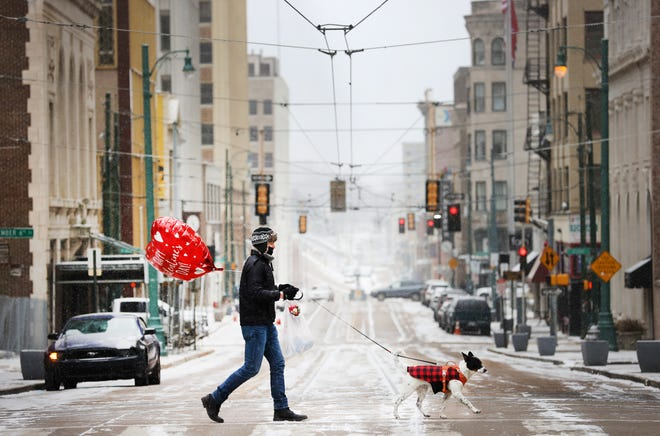Ross Hornish walks with his dog Miles across Madison Avenue, with a surprise Valentine's Day gift for his girlfriend, as below freezing temperatures and snow flurries cover Memphis, Tenn. on Sunday, Feb. 14, 2021.