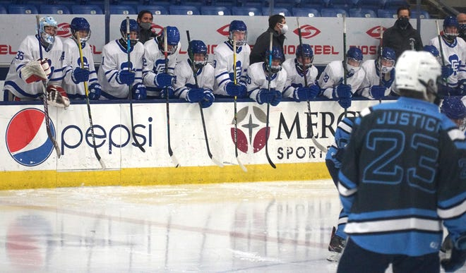 CC's bench pounds on the boards at the start of their game against Livonia Stevenson.