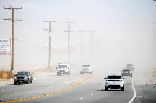 Blowing sand limits driver visability on Vista Chino in Palm Springs, Calif., on Saturday, February 13, 2021.