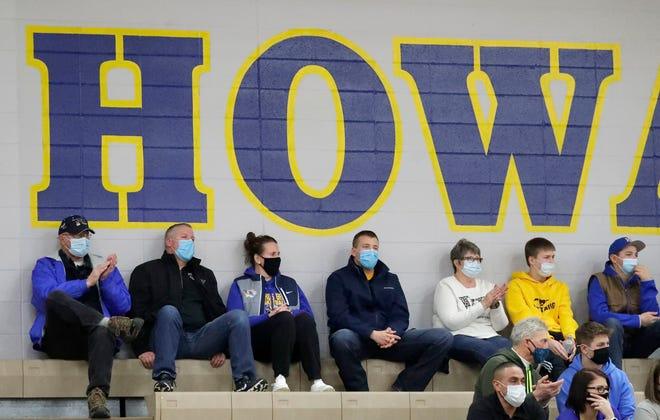 Masked basketball fans watch Kiel play Howards Grove on Feb. 13 in Howards Grove.