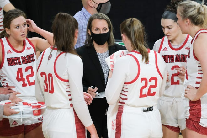 South Dakota head women's basketball coach Dawn Plitzuweit talks strategy with her players during a timeout in the first quarter of Sunday's matchup against the UND Fighting Hawks at the Betty Engelstad Sioux Center.