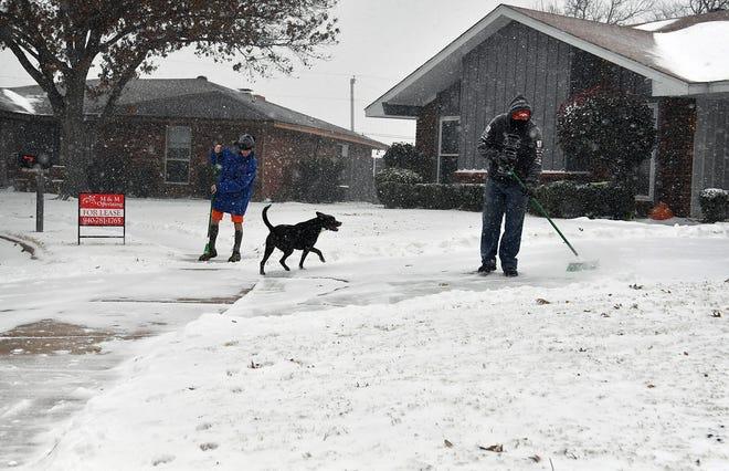Carlos Sandoval, right, and Julian Luna sweep snow Sunday as heavier snowfall began in southern Wichita Falls.