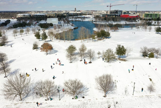 Dozens of people sled down a hill at Mueller Lake Park in Austin on Monday, Feb. 15, 2021. After a heavy night of snow, the National Weather Service has received reports from around Central Texas of snowfall totals as high as half a foot.
