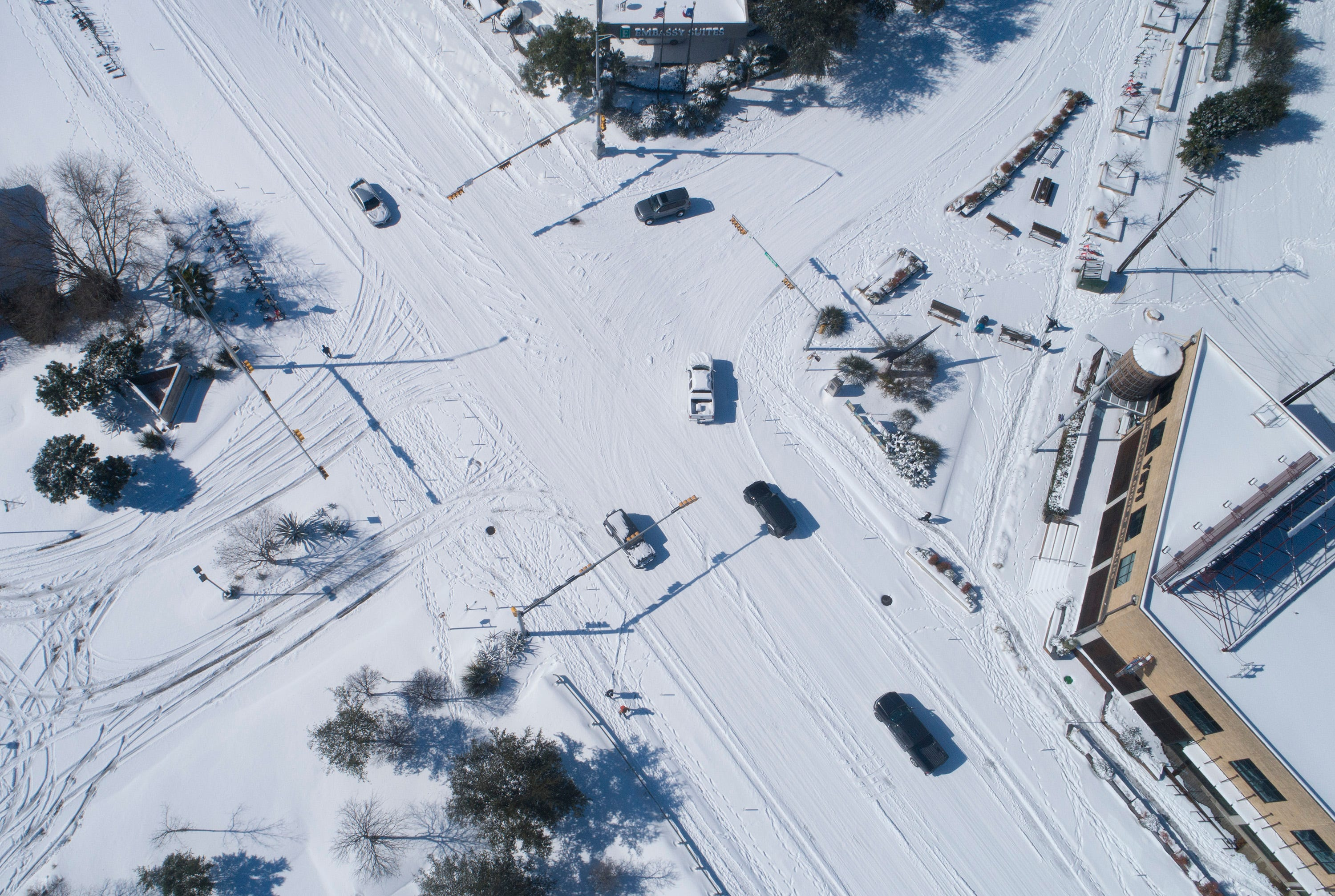 An overhead view of a cars driving through a snowy intersection.
