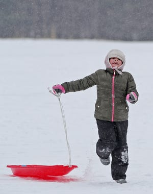 Natalia Bozickovic, 7 skips acorss the snow after coming down the Goodyear Heights Metropark sledding hill on Monday Feb. 15, 20201.