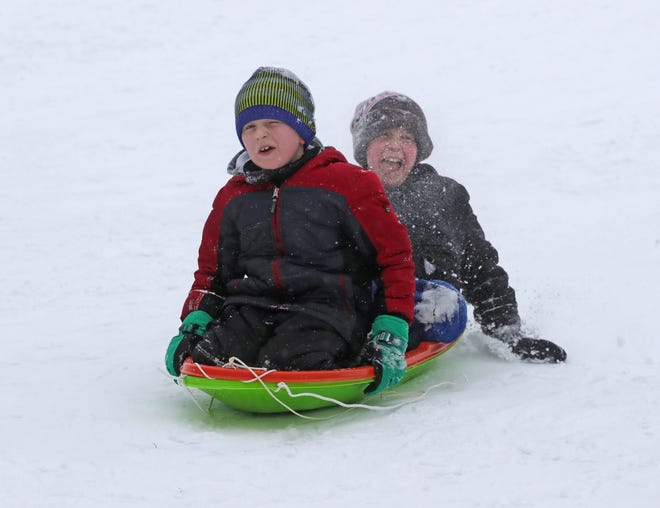 Evan Lerner, left, and Luca Milcetich head down a snow-covered hill at Hudson Springs Park.
