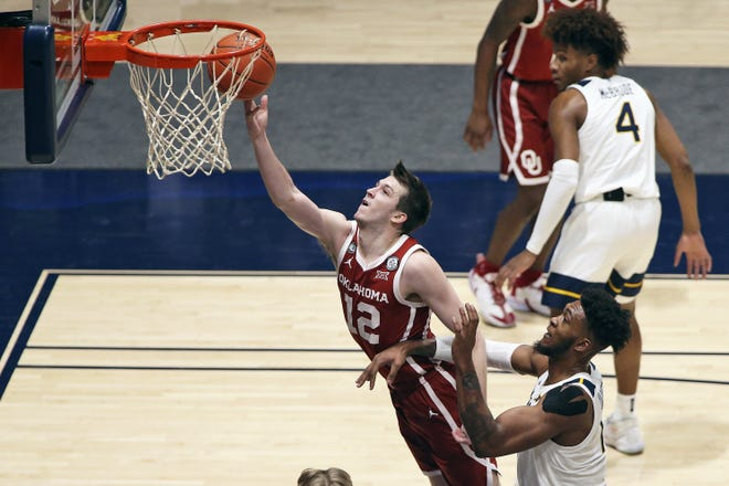 Oklahoma guard Austin Reaves shoots past West Virginia's Derek Culver during the second half of their game last Saturday. The Sooners won in Morgantown, W.Va.