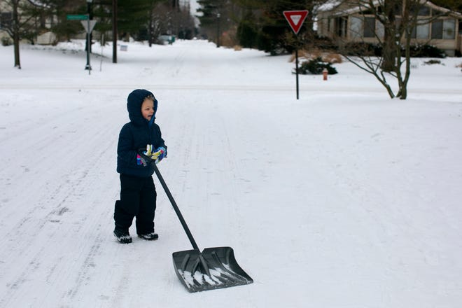 Three year old, Michael Harris, walks around his Clintonville neighborhood, with his mother Katie, shoveling as he goes, Monday, February 15, 2021.
