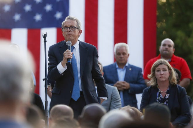 """A crowd shouted for Ohio Gov. MIke DeWine to """"do something"""" at a vigil after a gunman killed nine people in a mass shooting in Dayton on Aug. 4, 2019. Dayton Mayor Nan Whaley is at right."""