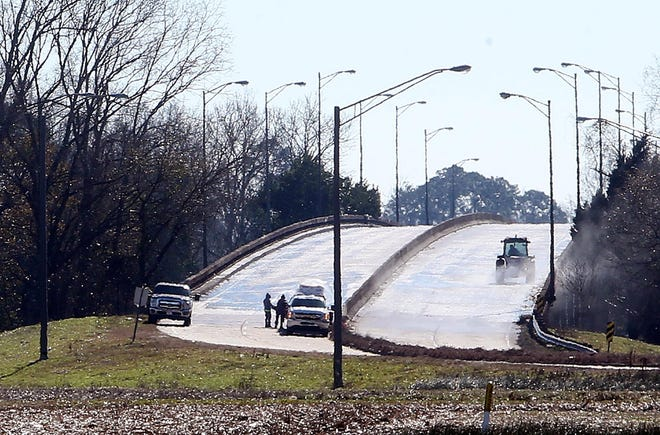 Crews work to treat the Schriever overpass ahead of a winter storm in 2018.