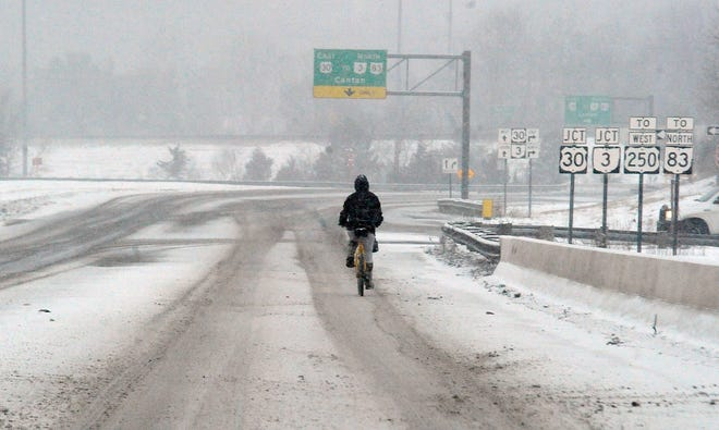 This Monday morning bicyclist is pedaling into a white oblivion as the snow continues to fall.