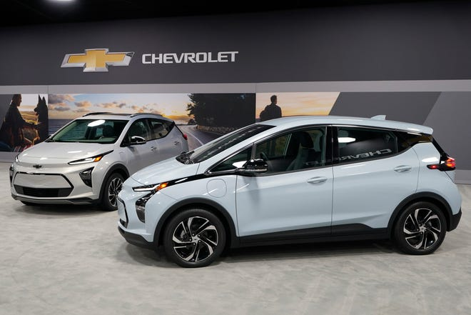 The 2022 Bolt EV, foreground, and EUV are displayed, Thursday, Feb. 11, in Milford, Mich. Whether people want them or not, automakers are rolling out multiple new electric vehicle models as the auto industry responds to stricter pollution regulations worldwide and calls to reduce emissions to fight climate change.